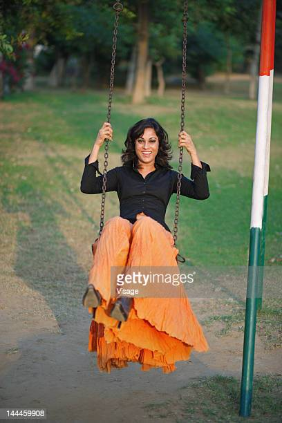 Woman sitting on a swing in a park, smiling