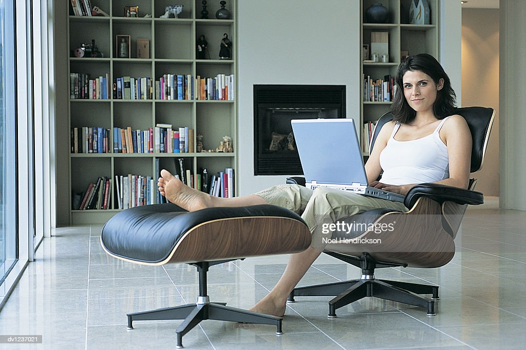 Woman Sitting On A Swivel Chair With Her Feet Up On A