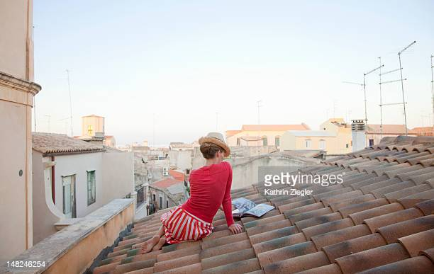 woman sitting on a tiled roof, reading cookbook