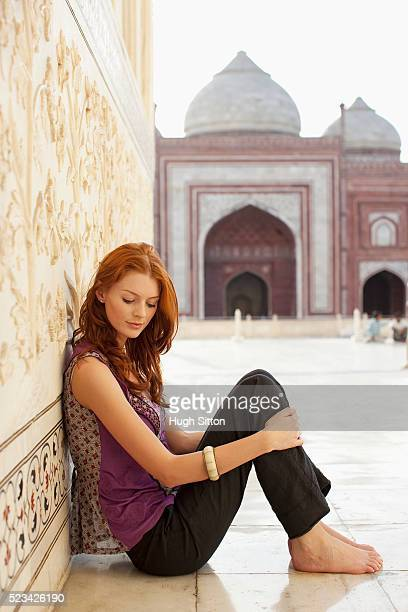 woman sitting on a walkway in the taj mahal - hugh sitton stockfoto's en -beelden