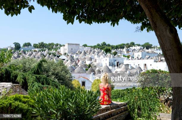 woman sitting on a wall, alberobello, apulia, italy - trulli stock photos and pictures