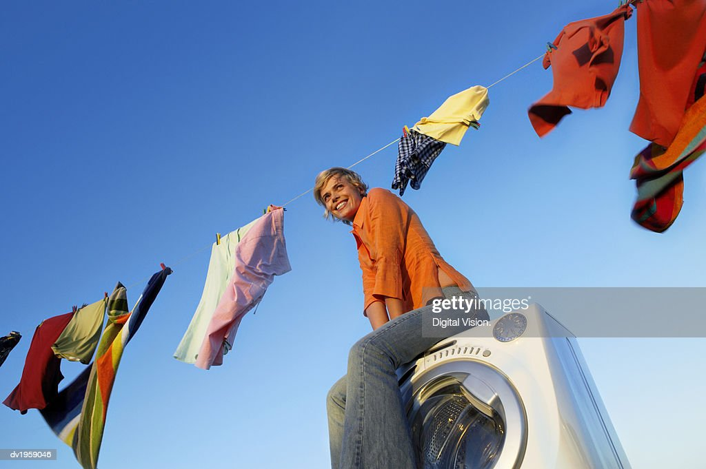 Woman Sitting on a Washing Machine With Laundry Hanging From a Washing Line in the Background : Stock Photo