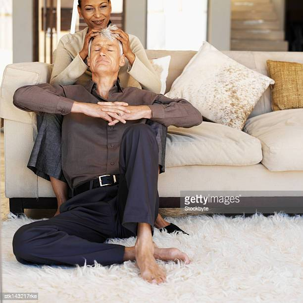 woman sitting on a white couch giving her husband a head rub - full body massage for men by women stock photos and pictures