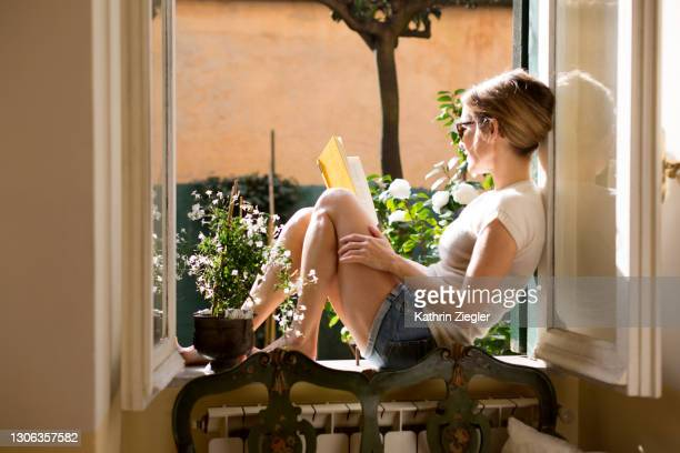 woman sitting on a windowsill, reading a book - book stock pictures, royalty-free photos & images