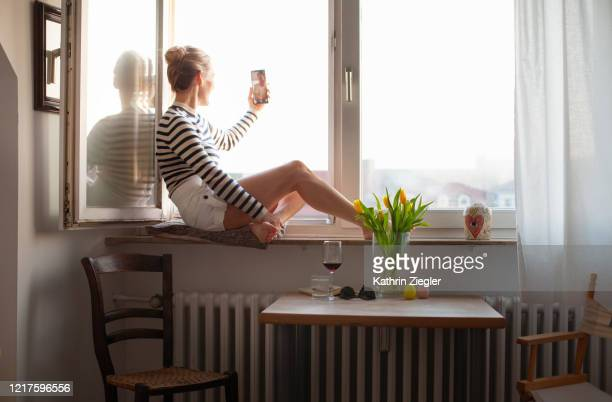 woman sitting on a windowsill, video chatting with family member - abstand halten infektionsvermeidung stock-fotos und bilder