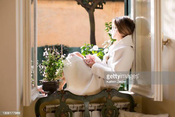 woman sitting on a windowsill with cup of coffee, wearing a bathrobe - 7894 stock pictures, royalty-free photos & images