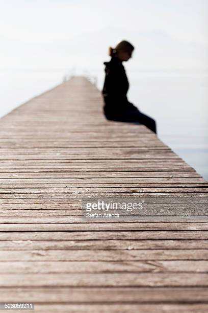 woman sitting on a wooden jetty, chiemsee lake, bavaria, germany, europe, publicground - depression sadness stock pictures, royalty-free photos & images