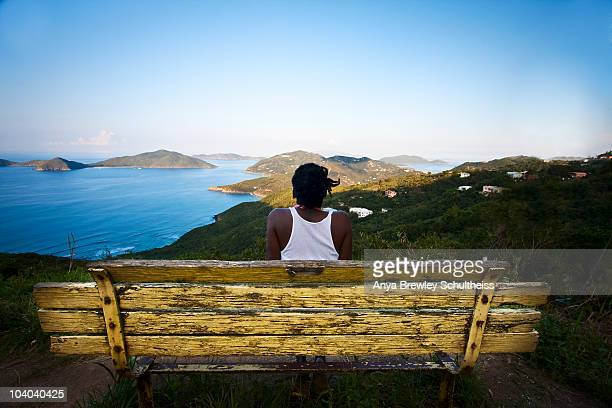 Woman sitting on a yellow bench enjoying the view