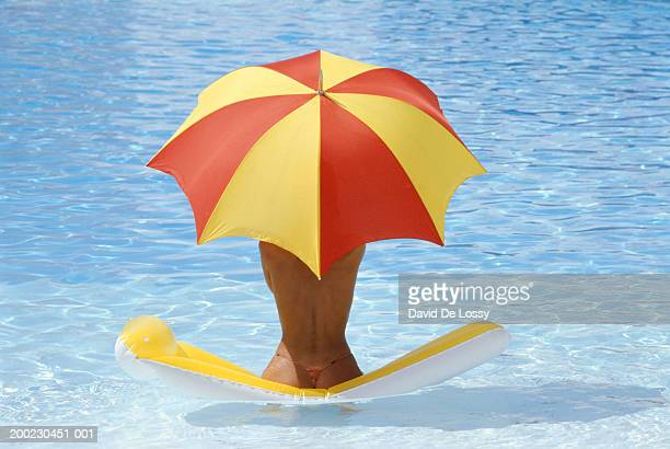 Woman sitting on airbed under umbrella in pool, rear view