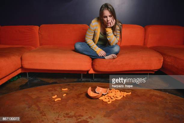 Woman sitting on an orange sofa looking at a broken bowl and cheese puffs.