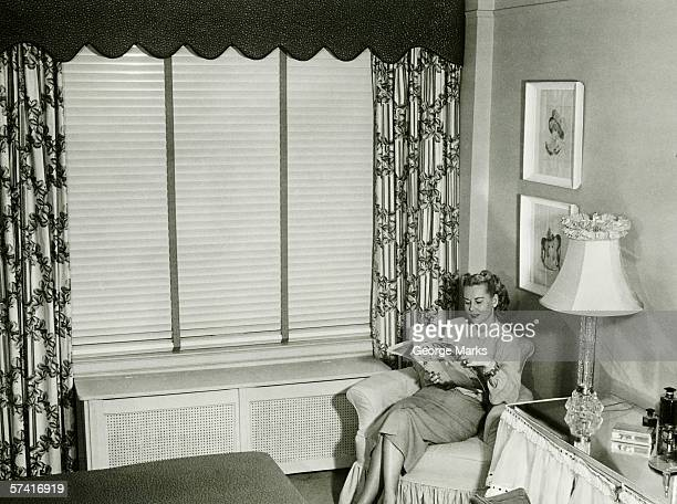 Woman sitting on armchair in bedroom, reading fashion magazine (B&W)