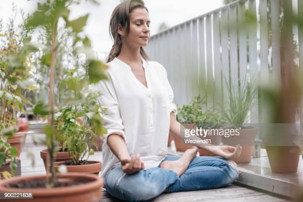 woman sitting on balcony practicing yoga - spiritualiteit stockfoto's en -beelden