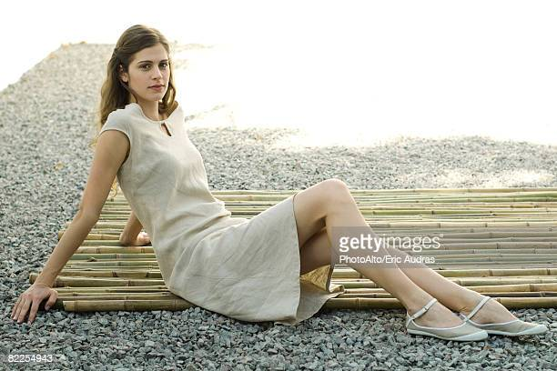 woman sitting on bamboo mat, smiling at camera, full length - solo ragazze foto e immagini stock