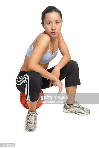 woman sitting on basketball, looking at camera - sleeveless top stock pictures, royalty-free photos & images