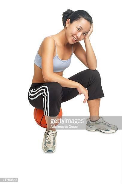 woman sitting on basketball, looking at camera, smiling - sleeveless top stock pictures, royalty-free photos & images
