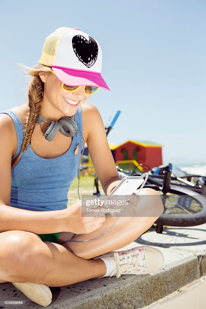 Woman sitting on beach and listening to music on smart phone : Stockfoto