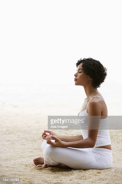 woman sitting on beach doing yoga, eyes closed.