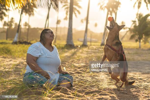 Woman sitting on beach sand playing with her dog