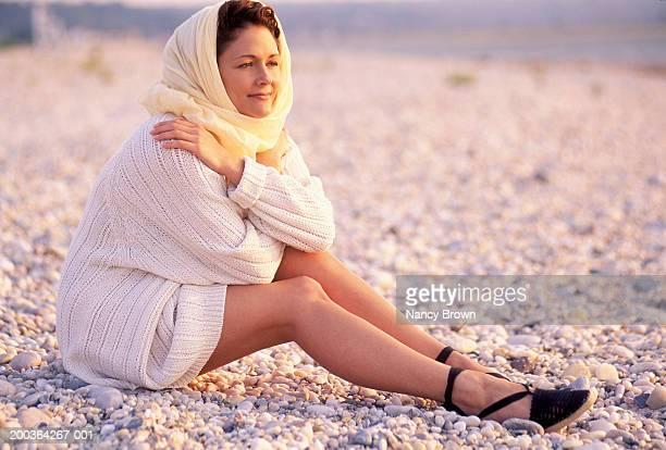 woman sitting on beach, side view, sunset - 頭にかぶるもの ストックフォトと画像