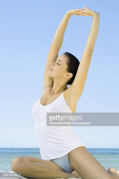 Woman sitting on beach, stretching arms overhead
