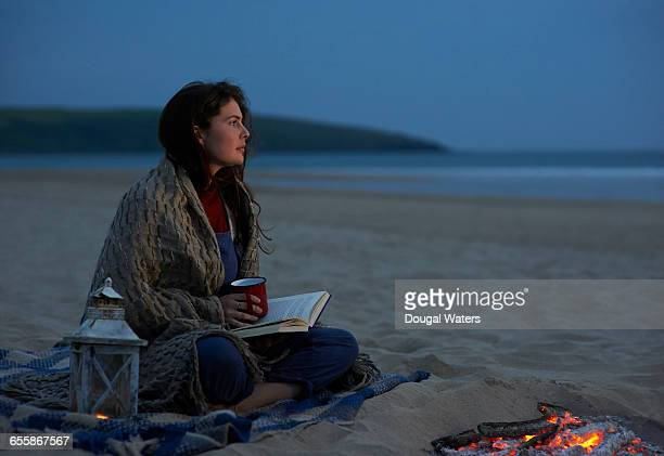 woman sitting on beach with book and bonfire. - dougal waters stock pictures, royalty-free photos & images