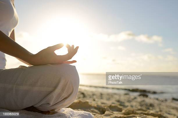 Woman Sitting On Beach With Yoga Lotus Position