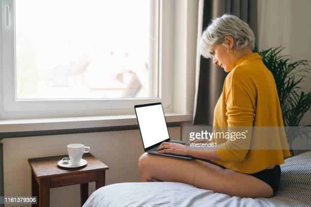 woman sitting on bed at home using laptop - frau in slip stock-fotos und bilder
