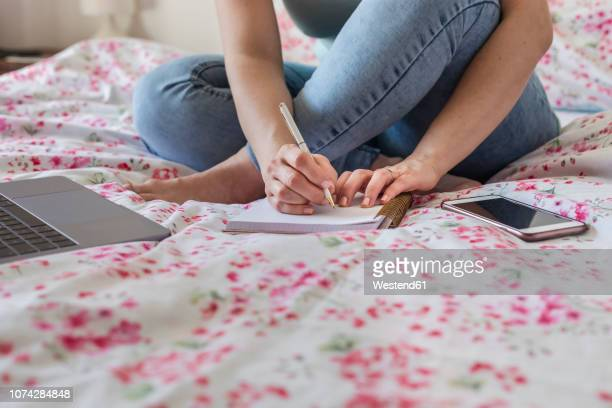 Woman sitting on bed at home working, partial view