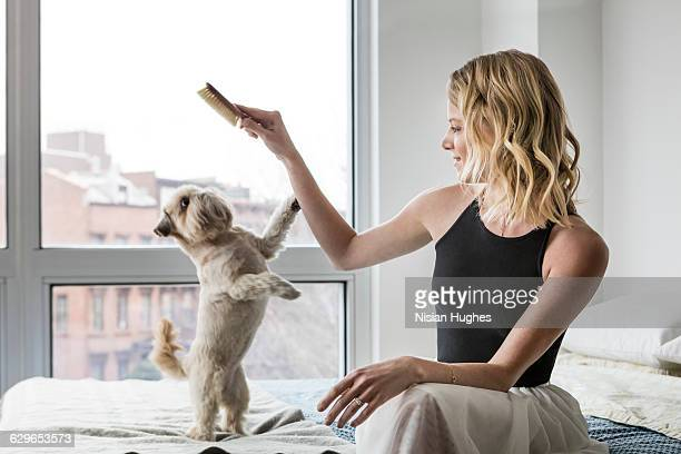 woman sitting on bed brushing her dog