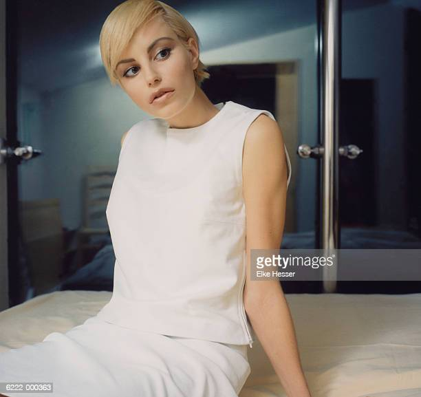 woman sitting on bed - sleeveless top stock pictures, royalty-free photos & images