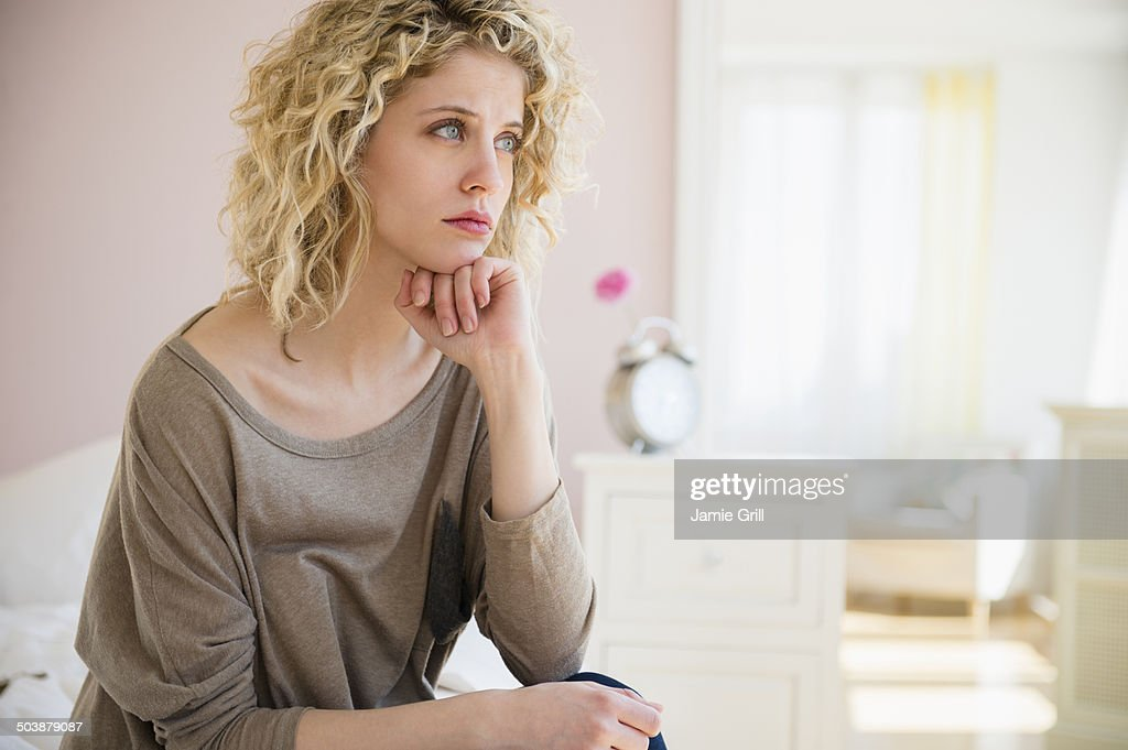 Woman sitting on bed, sad : Stock Photo