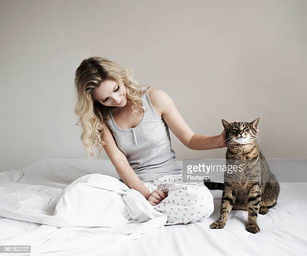 woman sitting on bed stroking her cat - nightdress stock pictures, royalty-free photos & images