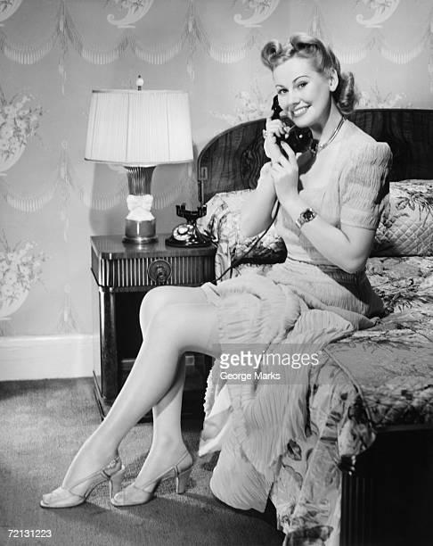Woman sitting on bed, talking on phone,  (B&W)