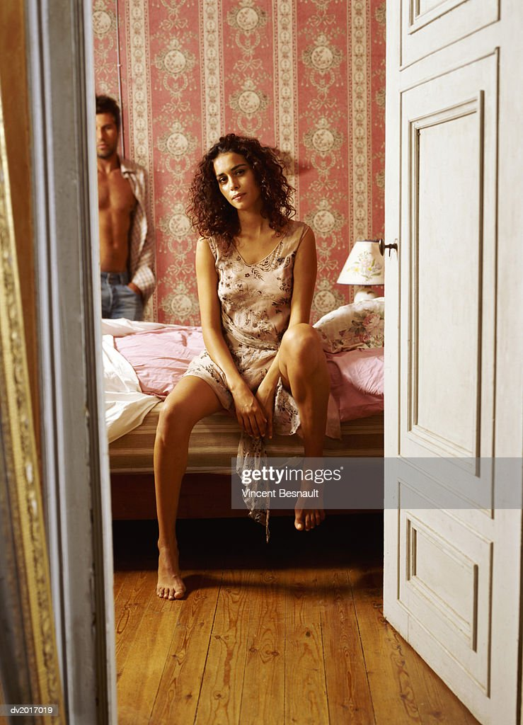 Woman Sitting on Bed, Topless Man in the Background : Stock Photo