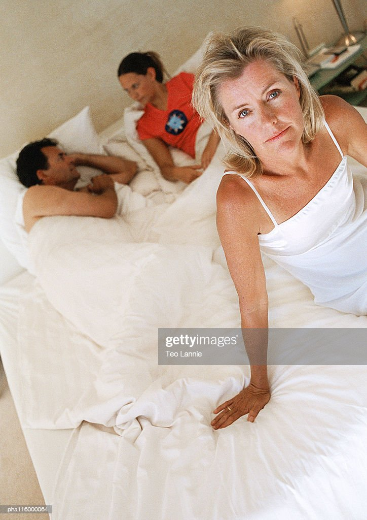 Woman sitting on bed, two people lying in bed in background : Stockfoto