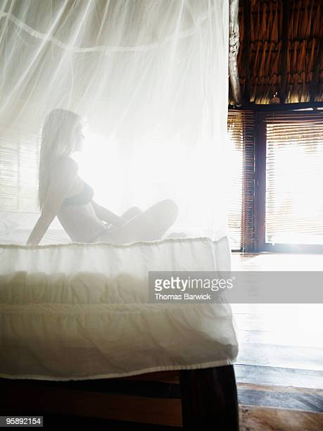Woman sitting on bed under mosquito netting