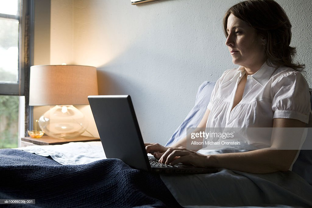 Woman sitting on bed using laptop : Stockfoto