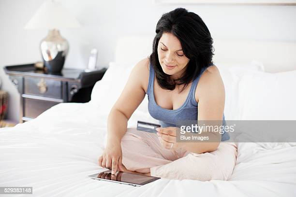 woman sitting on bed using tablet and credit card - chubby credit stock pictures, royalty-free photos & images