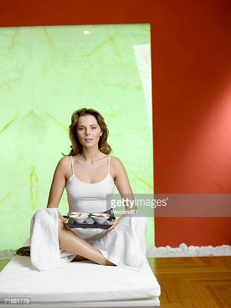 Woman sitting on bed with tray of bowl, portrait
