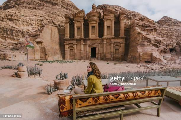 女性のベンチに座っていると、ペトラの修道院を見て - ヨルダン ストックフォトと画像
