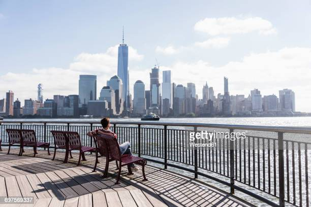 USA, woman sitting on bench at New Jersey waterfront with view to Manhattan