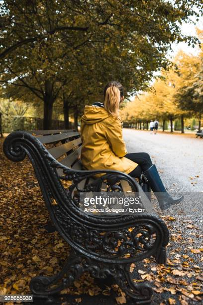 Woman Sitting On Bench At Park During Autumn
