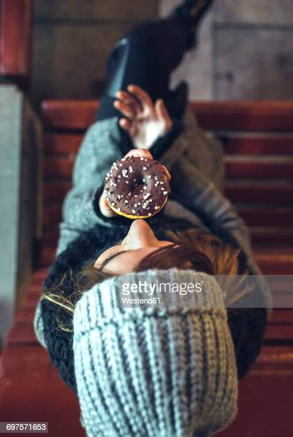 Woman sitting on bench eating doughnut with chocolate icing, top view
