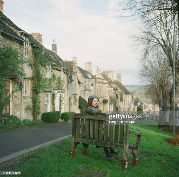 woman sitting on bench in beautiful old town,burford,oxfordshire,united kingdom,uk - village stock pictures, royalty-free photos & images