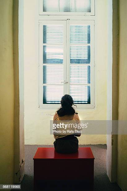 woman sitting on bench in front of closed window - woman prison stock-fotos und bilder
