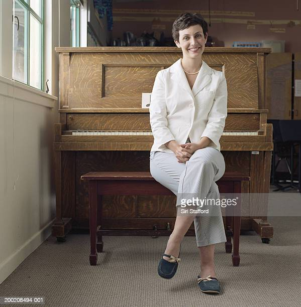 Woman sitting on bench in front of piano, portrait
