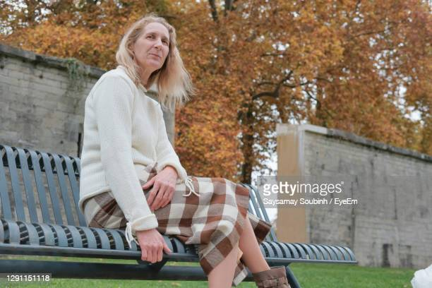 woman sitting on bench in park - ブザンソン ストックフォトと画像