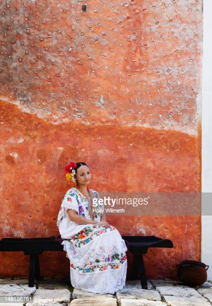 woman sitting on bench in traditional mexican clothing - merida mexico stock photos and pictures