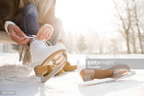 woman sitting on bench in winter landscape putting on ice skates - アイススケート ストックフォトと画像