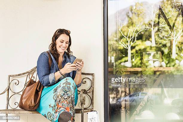 woman sitting on bench looking at smartphone smiling - world at your fingertips stock pictures, royalty-free photos & images
